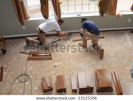 Hardwood Floor Installation - Construction workers install a hardwood floor over oriented strand board in a residence. - stock photo