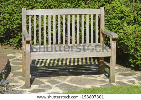 Hardwood seat placed in a sunny corner of a domestic garden - stock photo