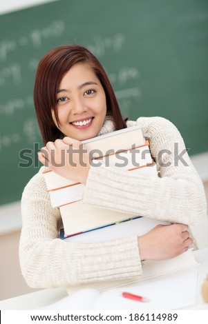 Hardworking beautiful young Asian student sitting in the classroom at college clutching a large stack of textbooks with a happy smile - stock photo