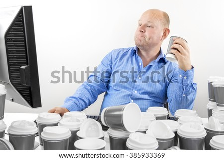 Hardworking business man drinks too much coffee - stock photo
