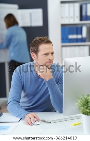 Hardworking businessman concentrating on his work staring at the monitor of his desktop computer with a serious thoughtful expression