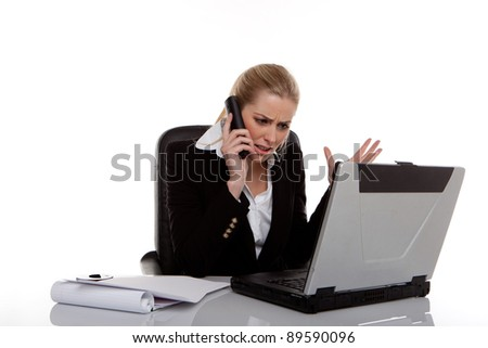 Hardworking Businesswoman Consulting Notes while seated at her desk next to laptop. - stock photo