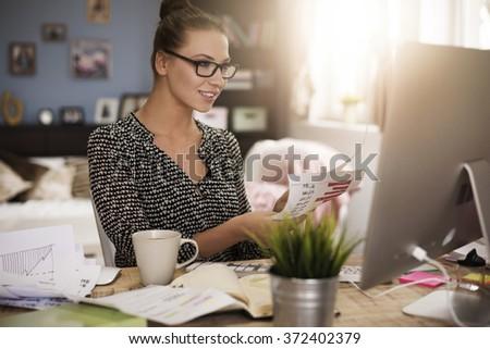 Hardworking woman analyzing important documents - stock photo