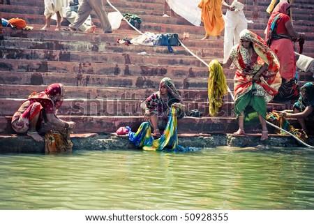 HARIDWAR - APRIL 11: Women washing their saris and clothing in holy Ganga river during Kumbha-mela festival. April 11, 2010 in Haridwar, India. - stock photo