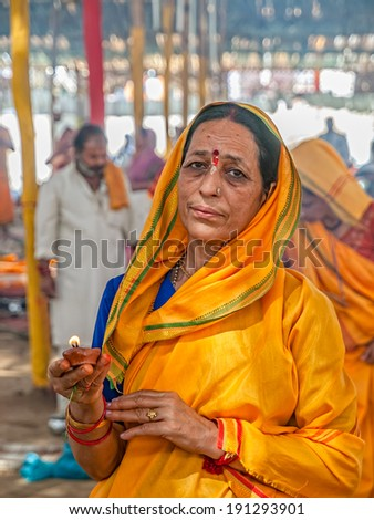 HARIDWAR, INDIA - APRIL 12, 2010: Hindu lady holds a candle on the Kumbh Mela a mass Hindu pilgrimage of faith in Which Hindus gather to bathe in the sacred river. - stock photo