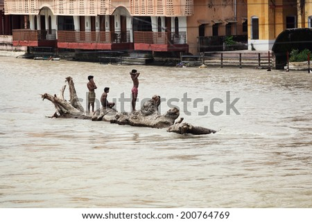 HARIDWAR, INDIA - AUGUST 28: Three unidentified indian teenage boys spend hot summer time  on Ganges River on August 28, 2012 in Haridwar - stock photo