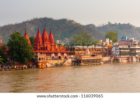HARIDWAR, INDIA - MAY 21: Unidentified Hindus gather at a pilgrimage spot near a red temple to bathe in the Ganges River for purification on May 21, 2009 in Hardiwar, India - stock photo