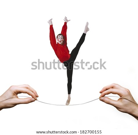 harlequin balancing on highwire tightrope - stock photo