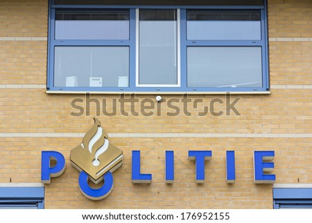 HARLINGEN, NETHERLANDS - CIRCA SEPTEMBER 2013: Logo of the Dutch police on the facade of police office in Harlingen circa September 2013. The police logo is part of the corporate identity since 1992. - stock photo