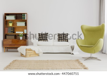 Harmonious and elegant living room decor, with a renovated modernist bookcase and a green egg chair - stock photo
