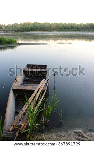 harmonious landscape for meditation: early morning on the Don river, Russia. Calm and quiet, fades to a haze over the water, the boat left there by the fishermen - stock photo