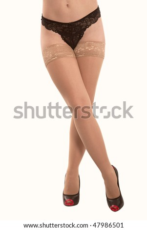 Harmonous legs  of the girl in stockings of corporal color on a white background