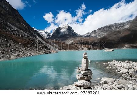 Harmony and balance: Pebble stack and Sacred Lake near Gokyo - stock photo