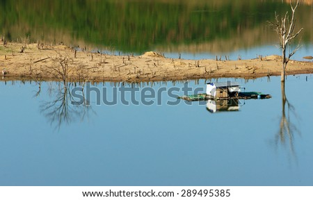 Harmony landscape of Asia countryside, lonely floating house on water, beautiful Nam Ka lake at Daklak, Viet nam. Reflection of dry tree, home on river make beautiful scene