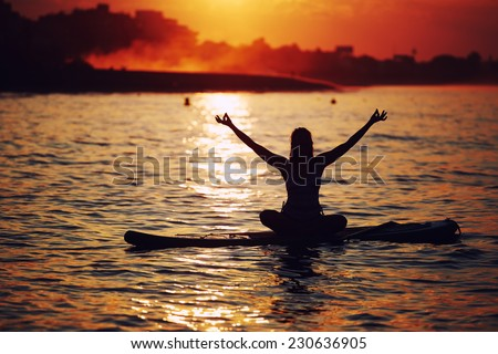 Harmony with the nature in yoga meditation, silhouette of woman doing paddle board yoga with beautiful orange sunset light reflected on the water, paddle surf yoga at the amazing sunset over the sea - stock photo
