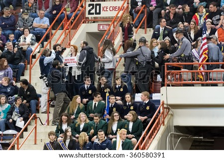 HARRISBURG, PENNSYLVANIA - JANUARY 09, 2016: Animal welfare activists are escorted out of the arena as they attempt to interrupt Governor Tom Wolf's opening ceremony speech at the Farm Show Complex. - stock photo