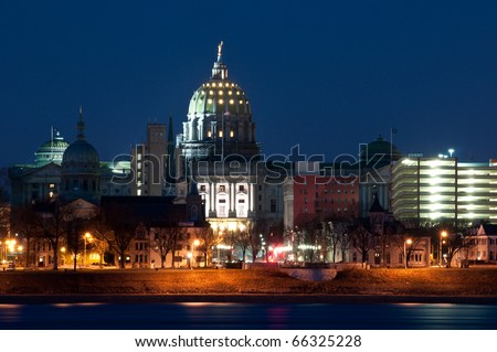 Harrisburg Pennsylvania Skyline at Night:  A view of Harrisburg, Pennsylvania's cityscape and state capital overlooking the Susquehanna River at night. - stock photo
