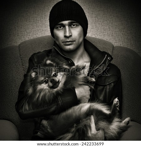 Harsh brutal man with Spitz dogs on their hands. Black and white photo in a dark style - stock photo