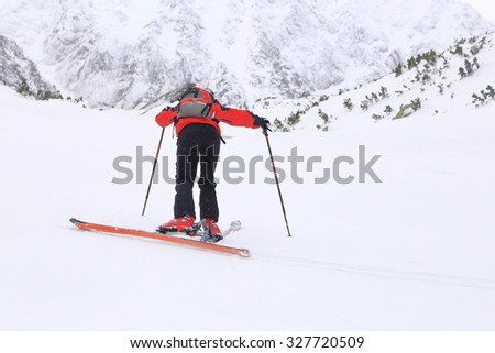 Harsh weather on the mountain and ski mountaineer climbing under the snowfall  - stock photo