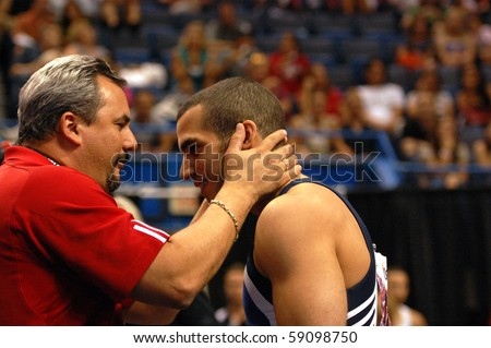 HARTFORD; CT - AUGUST 13: Gymnast Danell Leyva gets a hug from coach Yin Alvarez after his performance at the VISA Nationals Gymnastics Championships in Hartford; CT on August 13, 2010. - stock photo