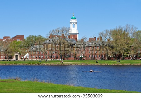 Harvard and the Charles. People jogging and walking along the riverbank in early spring. - stock photo