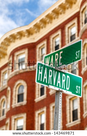 Harvard street sign with a classic red brick building in the background. Location: Harvard University in Cambridge, Massachusetts, USA. - stock photo