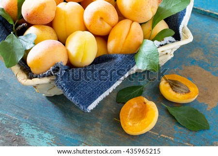 Harvest fresh ripe apricots in wicker basket on old wooden table, selective focus. - stock photo
