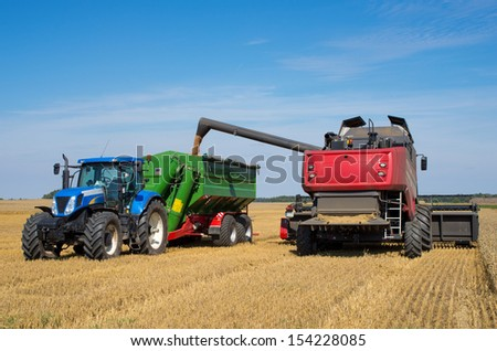 Harvest machine loading seeds in to trailer - stock photo