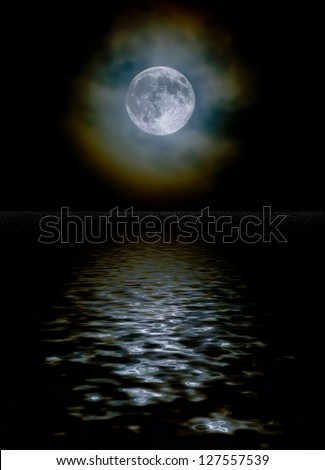 Harvest moon as seen through a light cloud layer with ice crystal light diffraction and a water reflection - stock photo