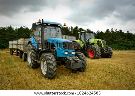 Harvest on a cloudy field with tractors and grain trailers