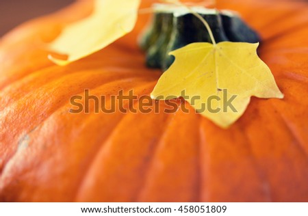 harvest, season and autumn concept - close up of pumpkin and autumn leaves - stock photo