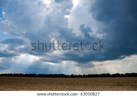 Harvested field, a beautiful stormy sky. Sunbeams. - stock photo