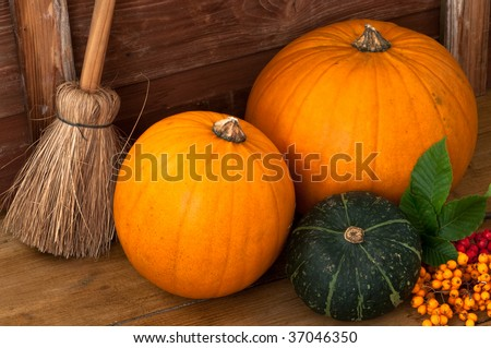 Harvested pumpkins on the floor with berries and broom