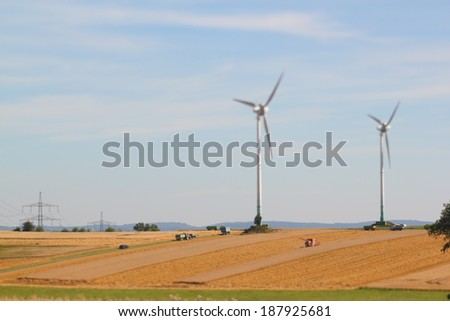 harvesting a barley field  with two wind turbines nearby - stock photo
