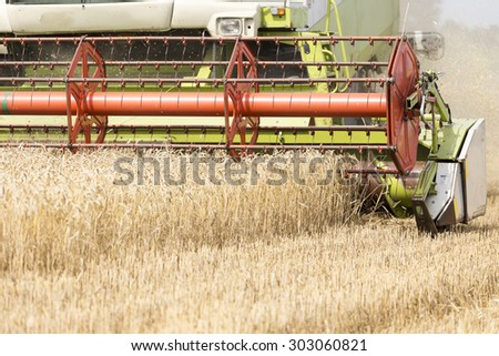 Harvesting machine on the wheat field - stock photo
