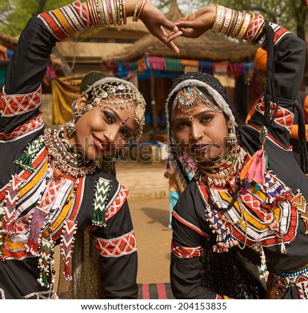 HARYANA, INDIA - FEBRUARY 12, 2009: Beautiful Kalbelia dancers in ornate black costumes trimmed with beads and sequins at the annual Sarujkund Fair near Delhi, India.