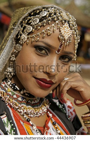 HARYANA, INDIA - FEBRUARY 12: Portrait of a beautiful Indian Kalbelia dancer in ornate headdress and traditional jewelery on February 12, 2009 at the Sarujkund Craft Fair in Haryana near Delhi, India.