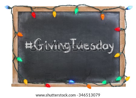 Hashtag Giving Tuesday written in white chalk on a black chalkboard surrounded with colorful lights isolated on white