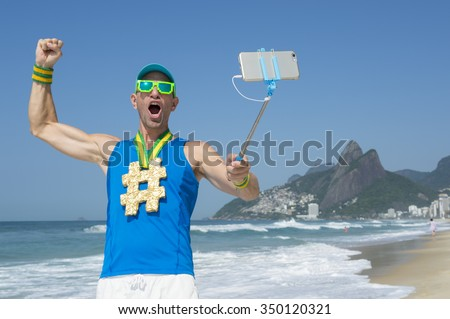 Hashtag gold medal athlete punching the air as he poses for a picture with his mobile phone on a selfie stick on Ipanema Beach in Rio de Janeiro, Brazil - stock photo