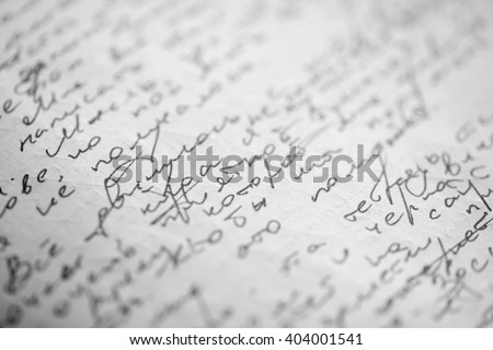 Hastily scrawled handwriting of cyrillic text using black ink on white paper, with visible imprints from writing on the obverse. - stock photo