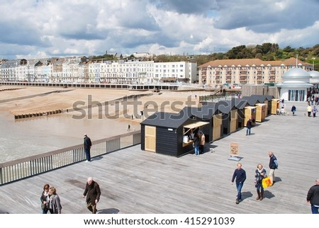 HASTINGS, ENGLAND - APRIL 30, 2016: People walk on the historic Victorian pier. Closed since 2008 and badly damaged by fire in 2010,  the landmark building reopened to the public on April 27, 2016.
