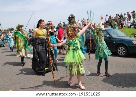 HASTINGS, ENGLAND - MAY 5, 2014: Costumed people take part in a parade on the West Hill during the annual Jack In The Green festival. The festival marks the May Day public holiday in Britain. - stock photo