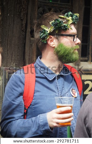 HASTINGS, UK - MAY 04, 2015: Man with green painted beard and garlands on his head drinks beer during the Jack in the Green Festival in Hastings, UK. - stock photo
