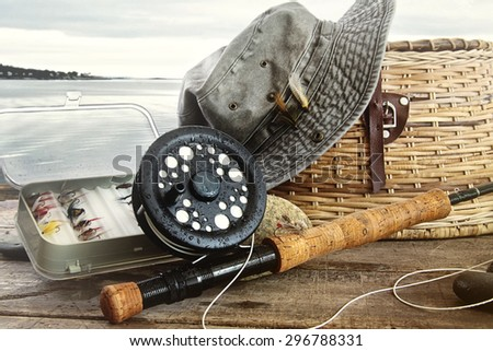 Hat and fly fishing gear on table near the water's edge - stock photo