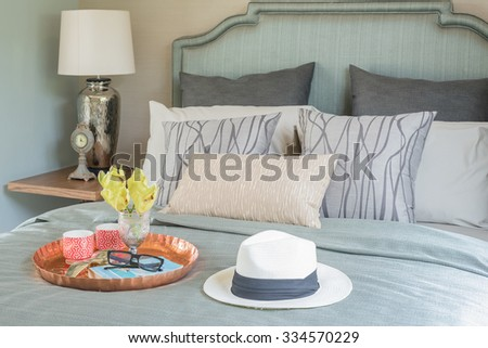 hat and tray with glass vase flower on bed in luxury bedroom