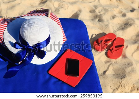 hat, bag, touch pad, mobile phone and flip flops on tropical beach, vacation cocept - stock photo
