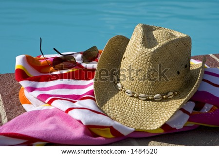 Hat, glasses and a beach towel beside a pool - stock photo