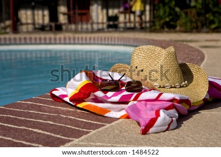 Hat, glasses and beach towel laying on the edge of a pool - stock photo