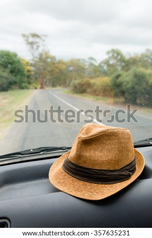 hat on the dashboard of a car on a road trip, can be flipped to a left hand drive position - stock photo