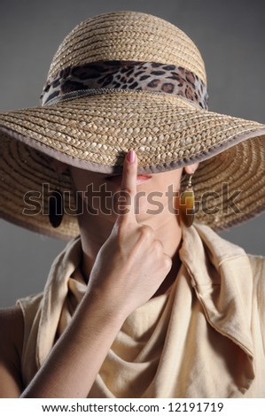 Hat - Portrait of elegant female covering her face with hat - stock photo